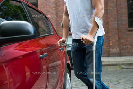Disabled Man Opening Door Of A Carの写真素材 [FYI00654250]