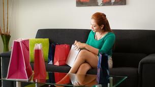 Latina Girl Peeps Into Shopping Bags On Sofa At Homeの写真素材 [FYI00654806]