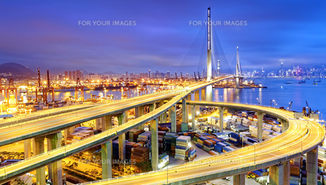 Container Cargo freight ship with working crane bridge in shipyard at dusk for Logistic Import Exportの写真素材 [FYI00655213]