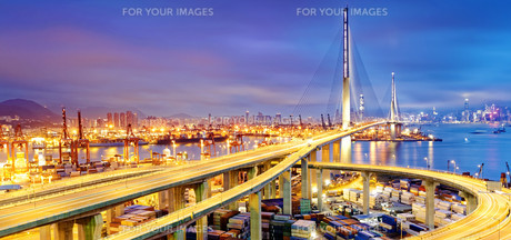 Container Cargo freight ship with working crane bridge in shipyard at dusk for Logistic Import Exportの写真素材 [FYI00655215]