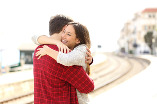 Couple hugging happy in a train stationの写真素材 [FYI00655370]