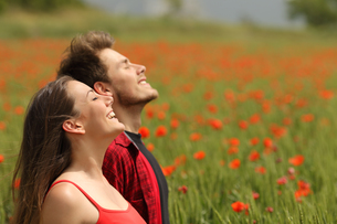 Happy couple breathing fresh air in a red fieldの写真素材 [FYI00655382]