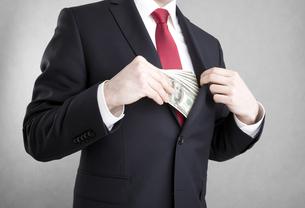 Corruption in business. Man putting money in suit jacket pocket.の写真素材 [FYI00656160]