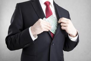 Corruption. Man putting polish money in suit jacket pocket.の写真素材 [FYI00656163]