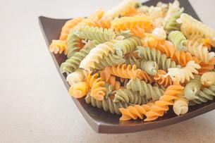Raw fusilli pasta on wooden trayの写真素材 [FYI00656751]