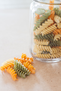 Raw fusilli pasta with glass bottleの写真素材 [FYI00656752]