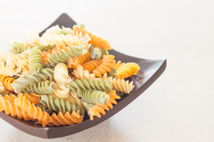 Raw fusilli pasta on wooden trayの写真素材 [FYI00656753]