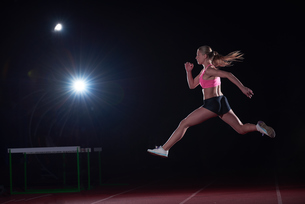 Athletic woman running on trackの写真素材 [FYI00656804]