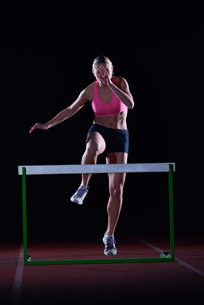 woman athlete jumping over a hurdlesの写真素材 [FYI00656809]