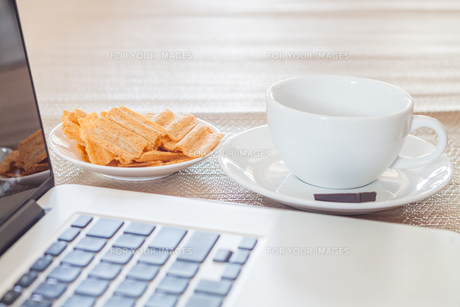 Laptop with coffee cup and snackの写真素材 [FYI00657098]
