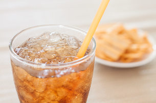 A glass of cola with snack on white plateの写真素材 [FYI00657104]