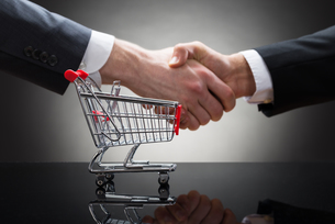 Businesspeople Shaking Hands With Mini Shopping Cartの写真素材 [FYI00657116]