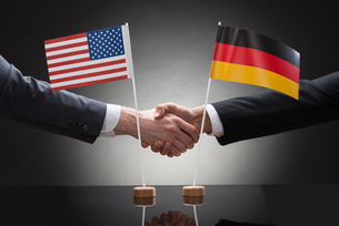 Businesspeople Shaking Hands With Us And Germany Flagsの写真素材 [FYI00657118]