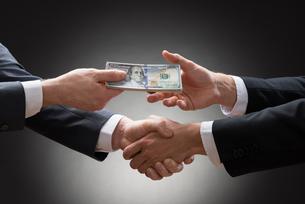 Businessmen Shaking Hands And Receiving Moneyの写真素材 [FYI00657125]