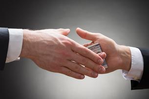 Businessman Hand Giving Bribeの写真素材 [FYI00657126]