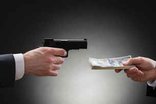 Businessman Giving Money To The Businessperson With Gunの写真素材 [FYI00657132]