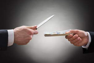 Businessman Giving Money To The Businessperson With Knifeの写真素材 [FYI00657138]