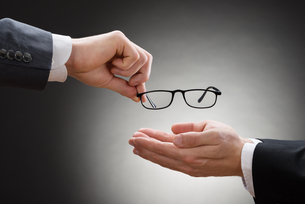 Businessman Giving Eye Glasses To His Colleagueの素材 [FYI00657145]