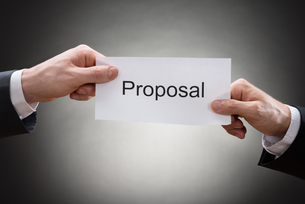Close-up Of Two Businessman's Hand Holding Proposal Paperの写真素材 [FYI00657155]