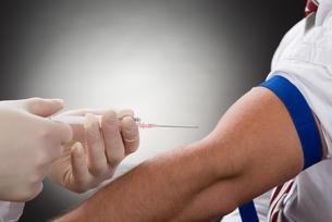 Doctor Injecting Syringe On Patient's Armの写真素材 [FYI00657189]