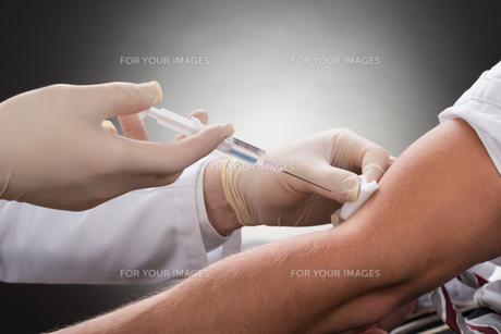 Doctor Injecting Syringe On Patient's Armの写真素材 [FYI00657191]