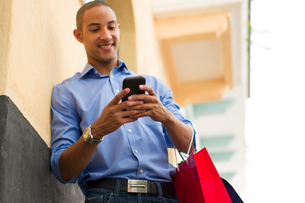 African American Man Text Messaging On Phone With Shopping Bagsの写真素材 [FYI00657928]