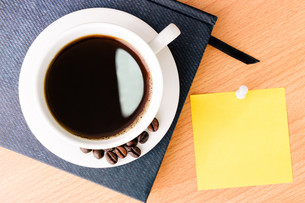 coffee and note pad on wood desk tableの写真素材 [FYI00658702]