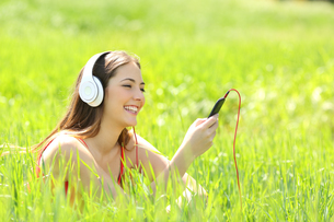 Girl listening music with headphones and smart phone in a fieldの写真素材 [FYI00659163]