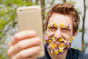 hipster man covered with flowers textingの写真素材 [FYI00659201]