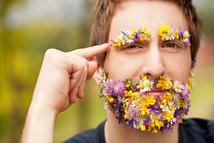 hipster face-covered with flowers thinkingの写真素材 [FYI00659202]