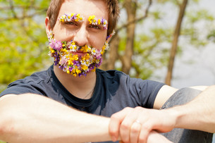 hipster self-confident man flowers covered faceの写真素材 [FYI00659203]