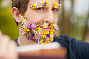 intense look of a flower covered hipster readingの写真素材 [FYI00659205]