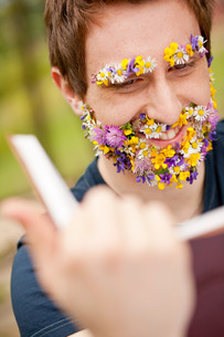 smiling hippy hipster reading face flower-coveredの写真素材 [FYI00659208]
