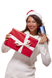 attractive woman with red santa claus hat with a big red christmas and bank card credit cardの写真素材 [FYI00659244]