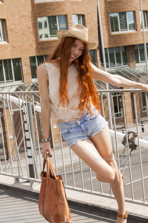 attractive young woman with long hair and straw hat outdoors rootenの写真素材 [FYI00659341]