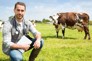 Portrait of a Young attractive veterinary in a pasture with cowsの写真素材 [FYI00659550]