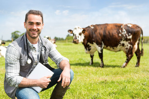 Portrait of a Young attractive veterinary in a pasture with cowsの写真素材 [FYI00659551]