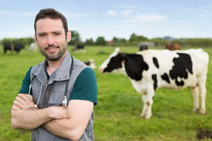 Portrait of a young attractive veterinary in a pasture with cowsの写真素材 [FYI00659561]
