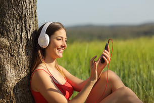 Girl listening to the music and downloading songs in a fieldの写真素材 [FYI00660082]