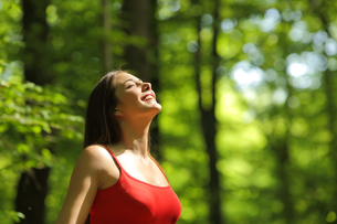 Woman breathing fresh air in the forestの写真素材 [FYI00660087]