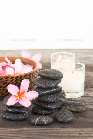 Plumeria flowers, black stones, floral water on wooden tableの素材 [FYI00660158]