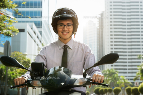 Chinese Businessman Commuter Using Scooter Motorcycle In Cityの写真素材 [FYI00660317]