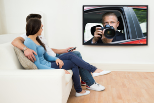 Couple In Livingroom Watching Televisionの写真素材 [FYI00660979]