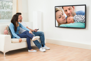 Young Couple In Livingroom Watching Televisionの写真素材 [FYI00660984]