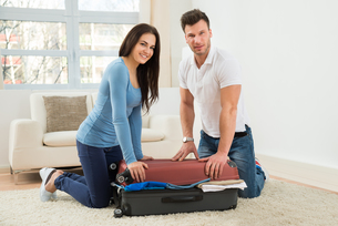 Couple Trying To Close Suitcase With To Much Clothesの写真素材 [FYI00661013]