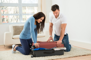 Couple Trying To Close Suitcase With To Much Clothesの写真素材 [FYI00661014]