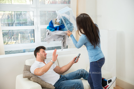 Woman Throwing Laundry On Husbandの写真素材 [FYI00661024]