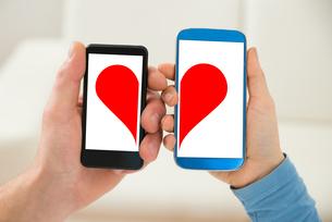 Couple Holding Cellphone With Half Heart Symbolの素材 [FYI00661053]