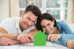 Young Couple Holding Green House Modelの写真素材 [FYI00661066]