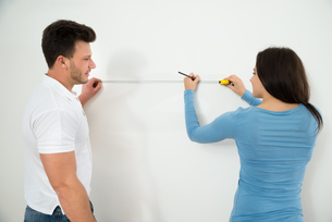Couple Measuring On Wall With Measuring Tapeの写真素材 [FYI00661083]